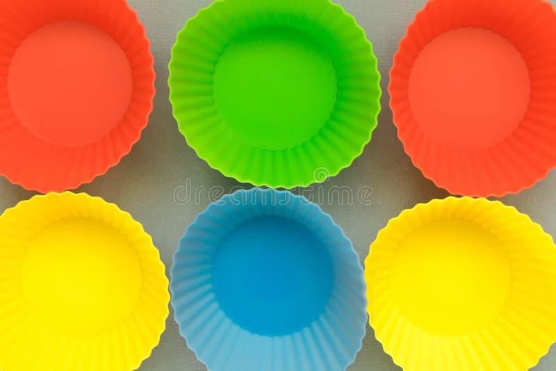 moldes de cozimento Multi-coloridos em um fundo claro fotos de stock