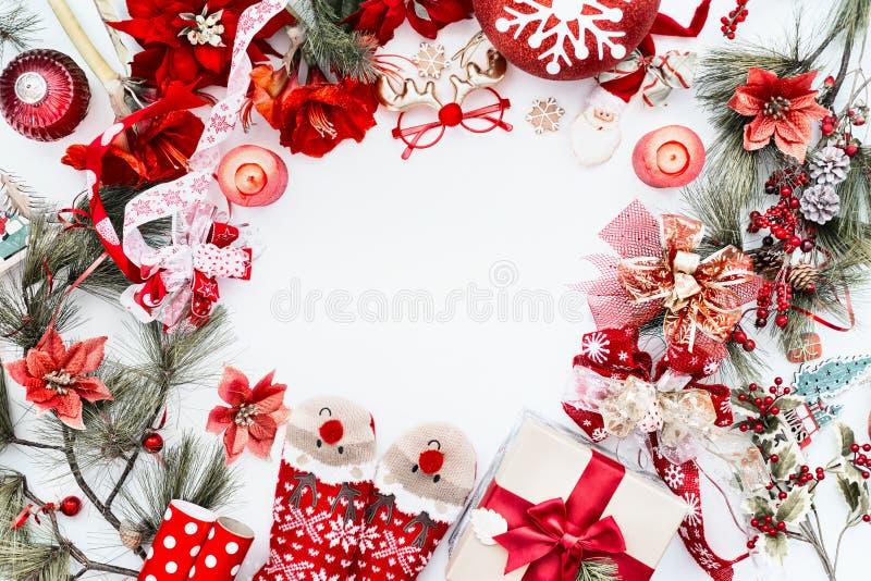 Moldura feita com decoração de Natal vermelha, meias de veados engraçadas e caixa de presentes em fundo branco com galhos e velas fotografia de stock royalty free