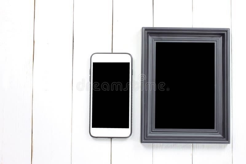 Moldura para retrato e smartphone no assoalho de madeira branco fotos de stock