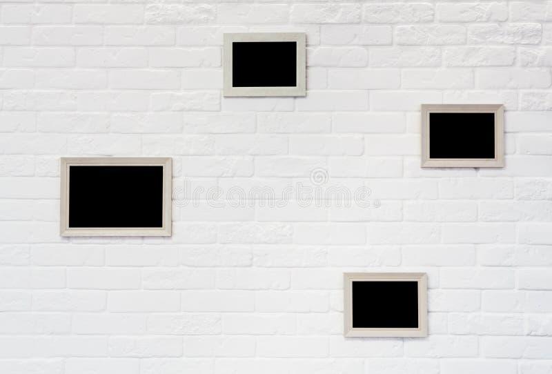 Moldura para retrato vazia na parede de tijolo branca imagem de stock