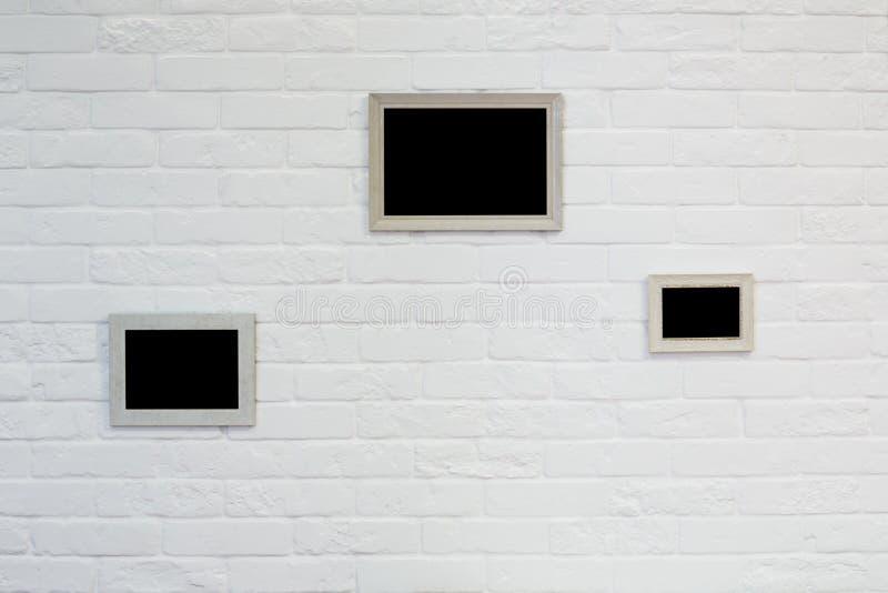 Moldura para retrato vazia na parede de tijolo branca fotografia de stock