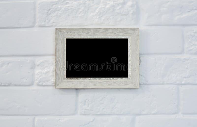 Moldura para retrato vazia na parede de tijolo branca imagens de stock royalty free