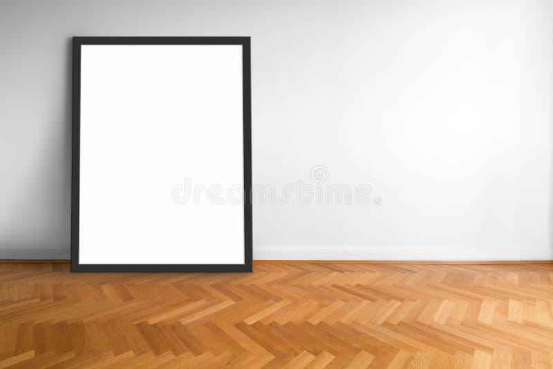Moldura para retrato vazia no fundo branco da parede do assoalho de madeira fotografia de stock royalty free