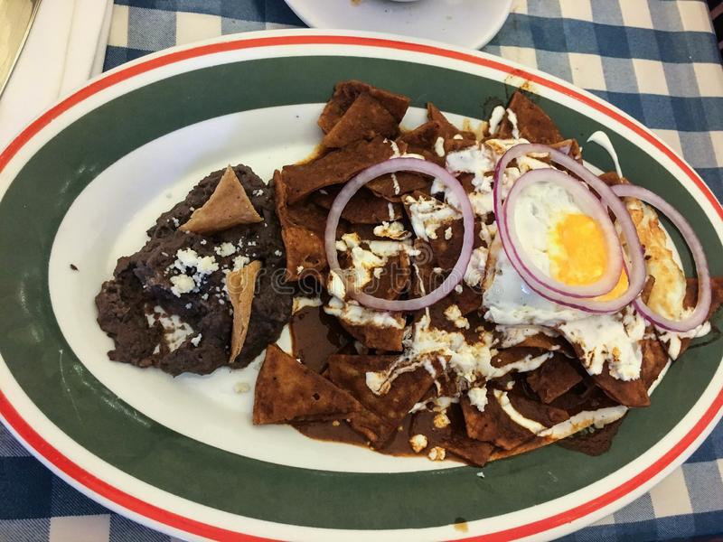 Mole chilaquiles with beans in colorful plate royalty free stock photos
