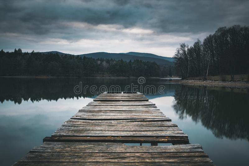 Mole pier on the lake. Wooden bridge in forest in spring time with blue lake. Lake for fishing with pier. Dark and Foggy lake royalty free stock photography