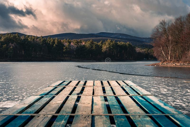 Mole pier on the lake. Wooden bridge in forest in winter time with blue frozen lake. Lake for fishing with pier. Dark lake ice stock images