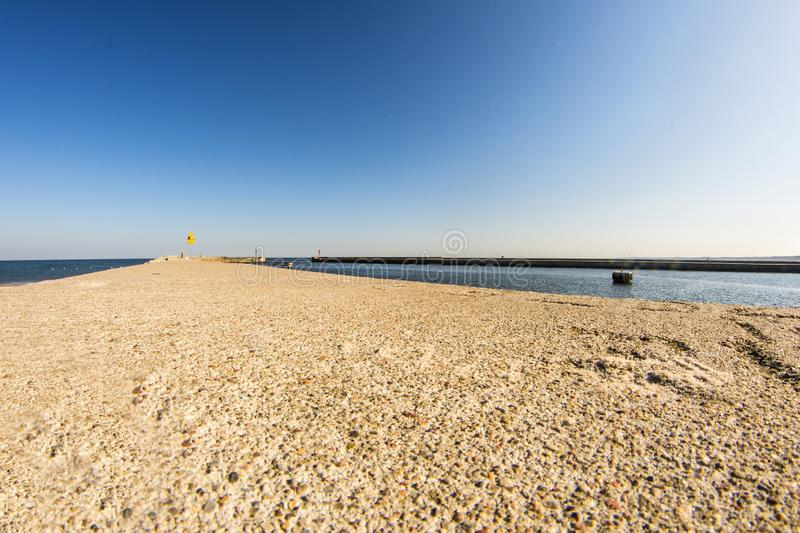 Mole of Ustka, Poland, wall with Baltis sea. And blue sky stock image
