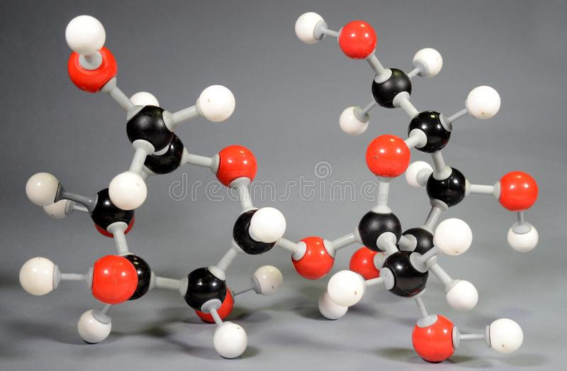 Molecule model of sugar C12H22O11. Red is oxygen, black is carbon, and white is hydrogen royalty free stock image