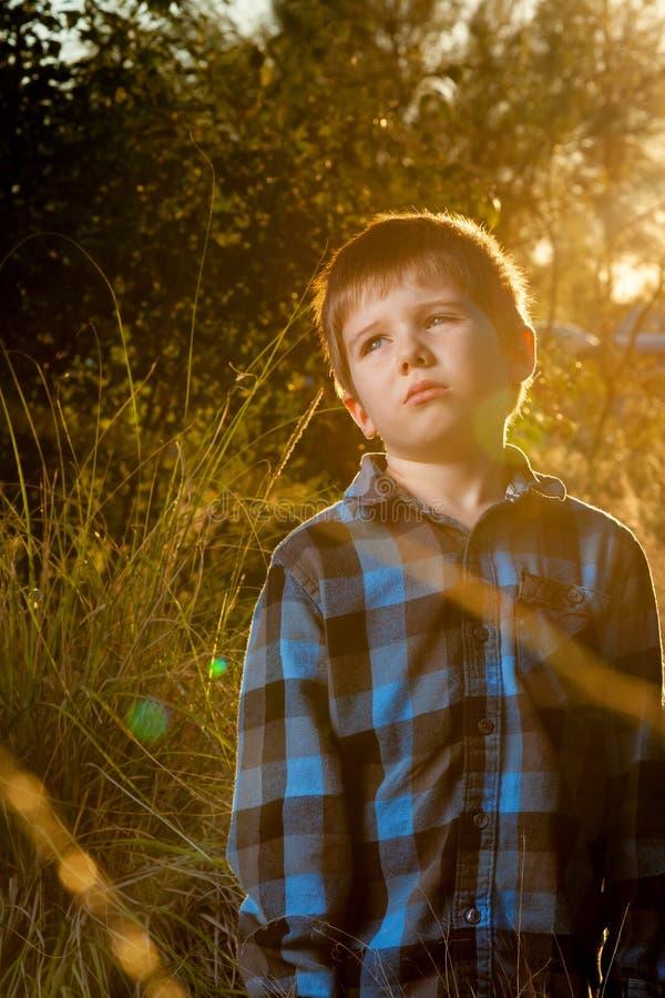 Molestado cansó Little Boy en la última hora de la tarde Sun con la llamarada y el Co imagen de archivo libre de regalías