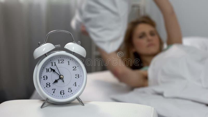 Molestado con la almohada que lanza de la señora del despertador, privación del sueño, tensión de la mañana fotografía de archivo