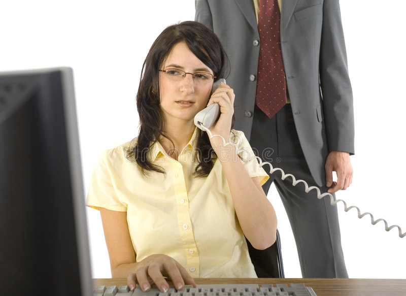 Molestation in work?. Young businesswoman sitting at desk, talking on phone. Working on computer. Man in suit standing behind her. White background stock photo