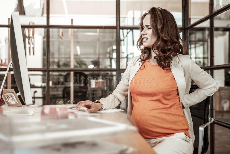 Moleste a la mujer embarazada que frota su parte posterior mientras que siente espalda dolor foto de archivo libre de regalías