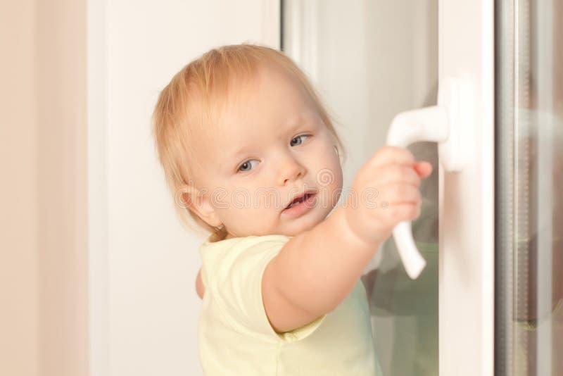 Molette adorable d'hublot de fixation de fille d'enfant en bas âge photographie stock