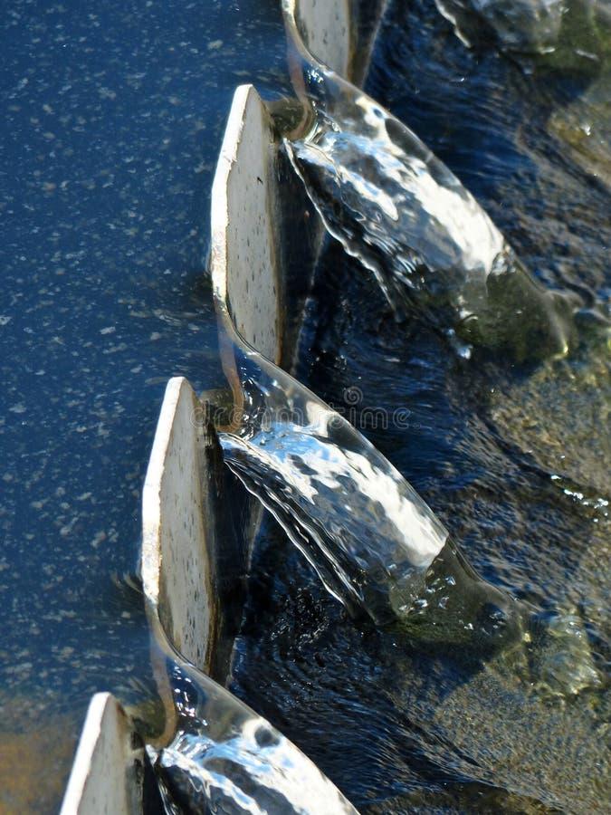 Molhe através de um Weir após o tratamento biológico em uma planta de tratamento de águas residuais fotos de stock