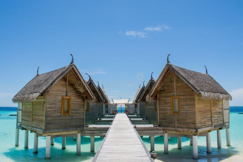 Molhe bungalos na praia tópica em Maldivas imagem de stock royalty free