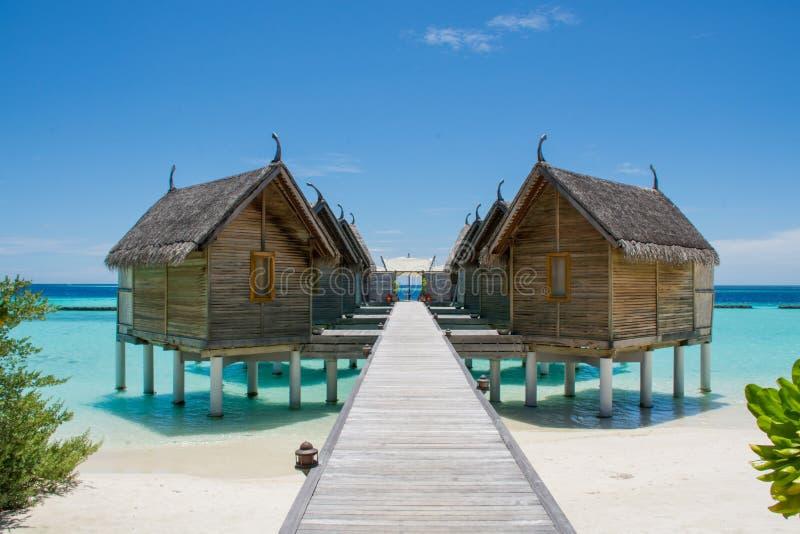 Molhe casas de campo na praia tópica em Maldivas fotografia de stock