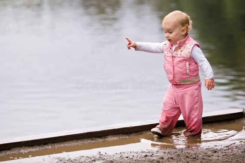 molhe a criança da menina na poça foto de stock royalty free