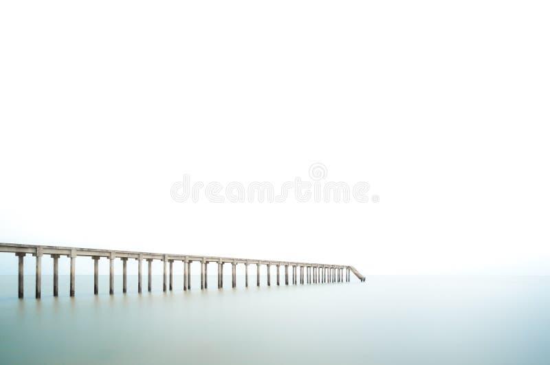 Molhe da pesca na exposição longa e no céu branco, espaço negativo fotografia de stock royalty free