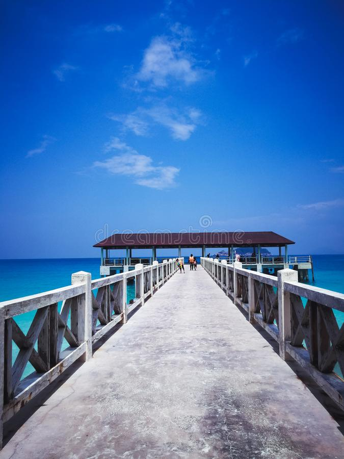 Molhe de madeira no meio-dia sob céus azuis claros com passeio dos povos fotos de stock royalty free