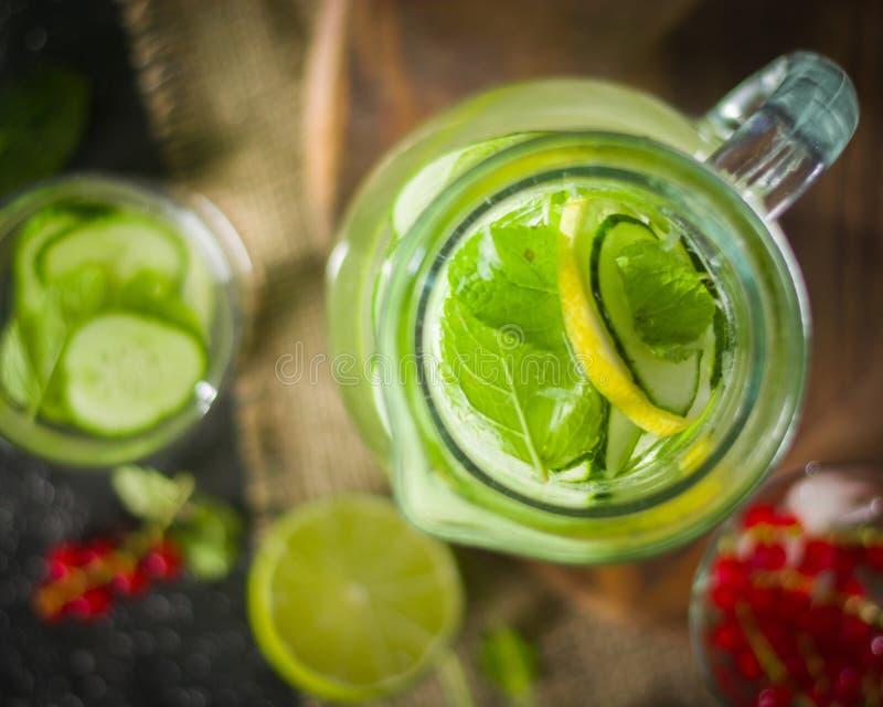 Molhe a desintoxicação em um frasco de vidro e em um vidro Hortelã e bagas verdes frescas Um refrescamento e uma bebida saudável imagens de stock royalty free