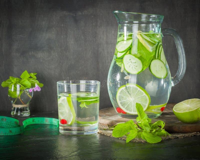 Molhe a desintoxicação em um frasco de vidro e em um vidro Hortelã e bagas verdes frescas Um refrescamento e uma bebida saudável fotos de stock royalty free