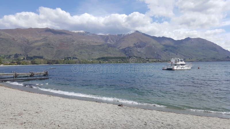 Molhe e barco no lago Wanaka, Nova Zelândia fotos de stock royalty free