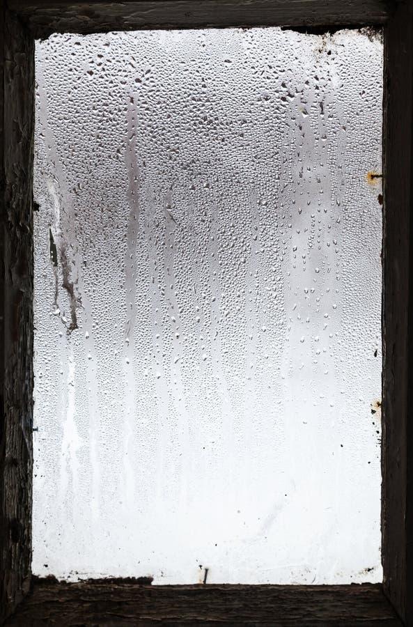molhe gotas da neve de derretimento na janela misted imagens de stock