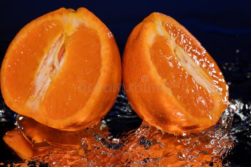 Molhe gotas em torno do mandarino no fundo do azul do espelho imagem de stock royalty free