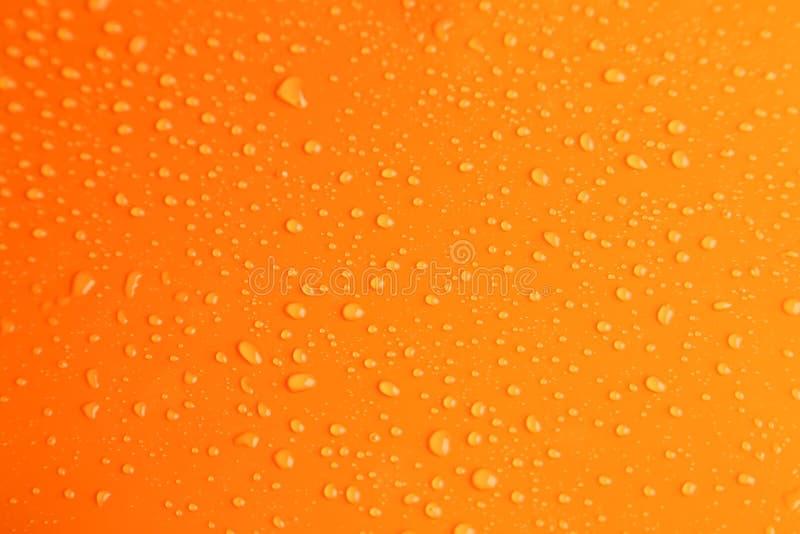 Molhe gotas no fundo alaranjado, fim acima imagem de stock royalty free