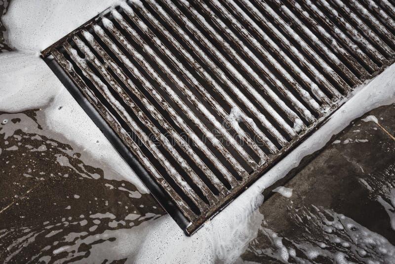 Molhe a grade na lavagem de carros, espuma da drenagem que flui no dissipador imagem de stock royalty free