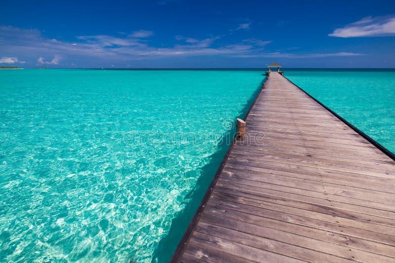 Molhe longo sobre a lagoa em Maldivas com agua potável surpreendente imagem de stock royalty free