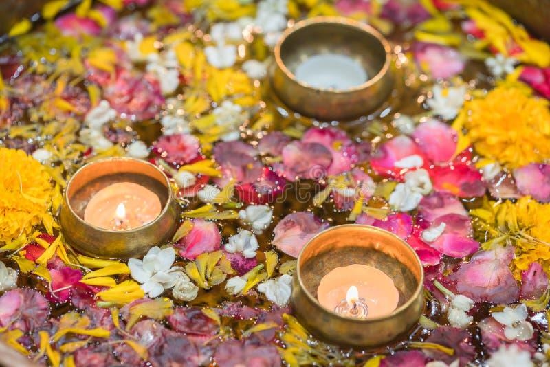 Molhe na bacia misturada com a vela e floresça a corola para Songkran imagem de stock royalty free