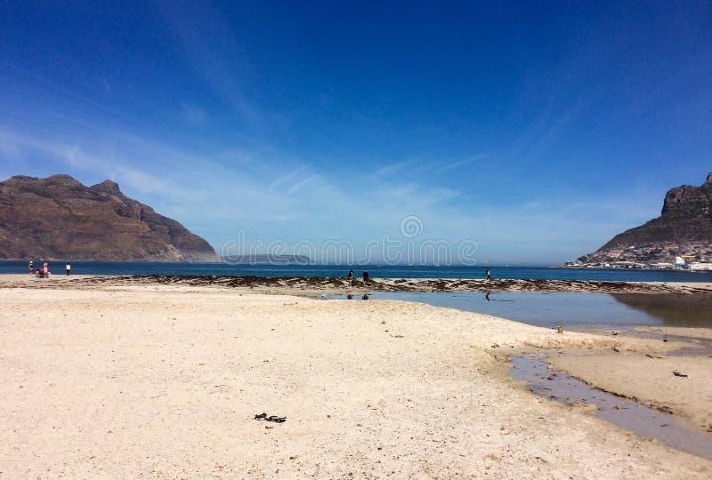 Molhe na praia, no mar, no céu e na montanha imagem de stock