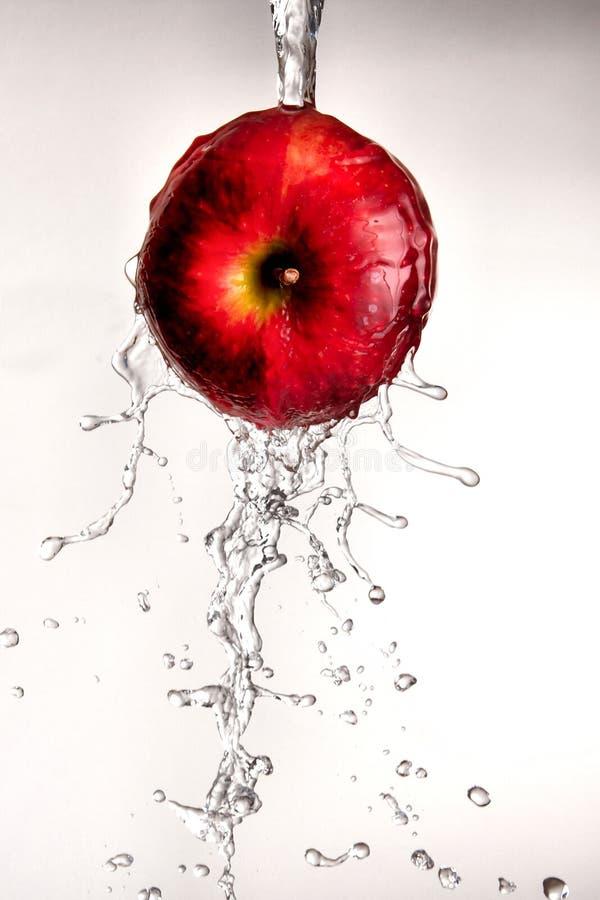 Molhe o derramamento fora da maçã vermelha. fotografia de stock