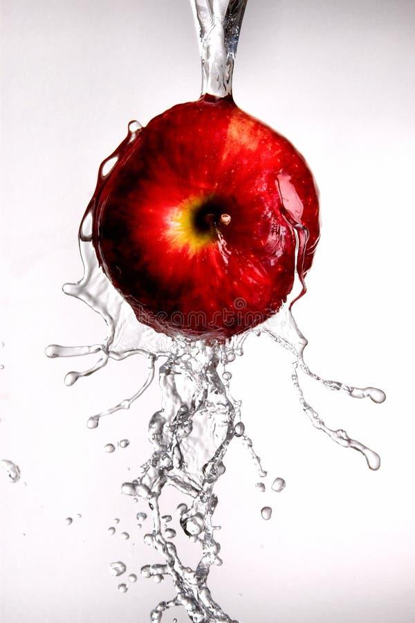 Molhe o derramamento fora da maçã vermelha. fotos de stock royalty free