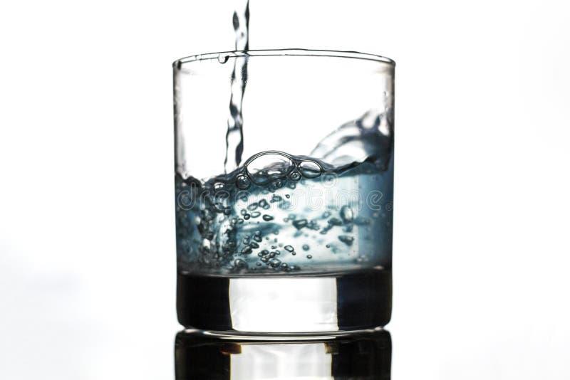 Molhe o espirro do vidro isolado no fundo branco imagens de stock