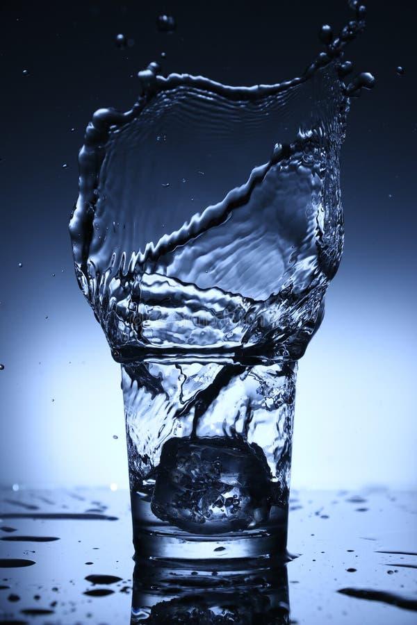 Molhe o respingo em um vidro da queda dos cubos de gelo fotografia de stock royalty free