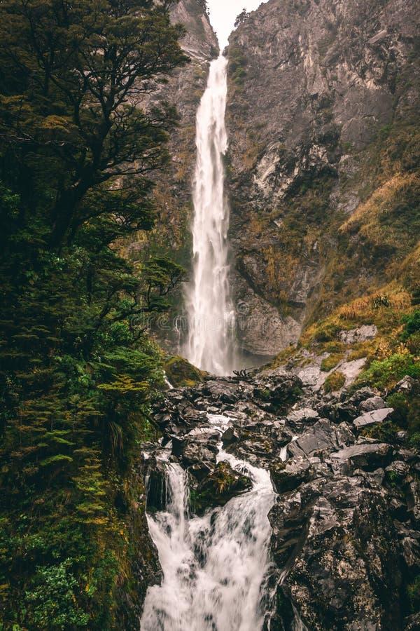 Molhe a queda das montanhas que correm no córrego com rochas escuras foto de stock