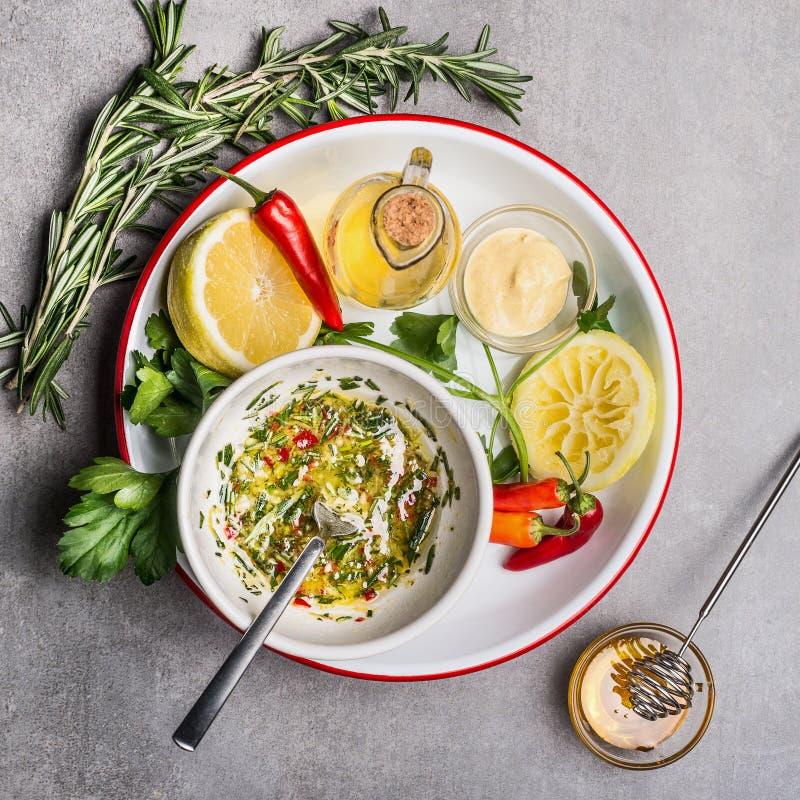 Molho caseiro do molho ou da salada na bacia com ingredientes: ervas, óleo, limão e mel frescos, vista superior, fim acima Saudáv fotos de stock