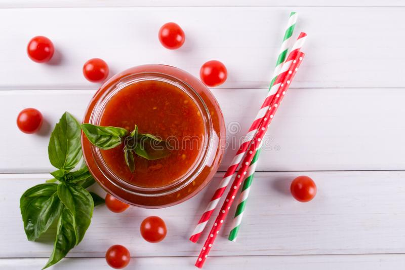 Molho da ketchup de tomate com tomates de cereja e pimentas de pimentão encarnados, alho e ervas em um frasco de vidro no fundo b foto de stock royalty free