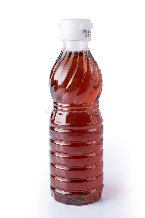 Molho de peixes na garrafa plástica no fundo branco fotografia de stock royalty free