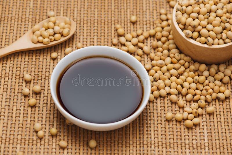 Molho de soja e feijão da soja na tabela de madeira imagens de stock