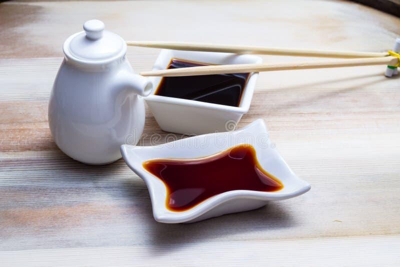 Molho de soja em um prato branco e em hashis fotografia de stock