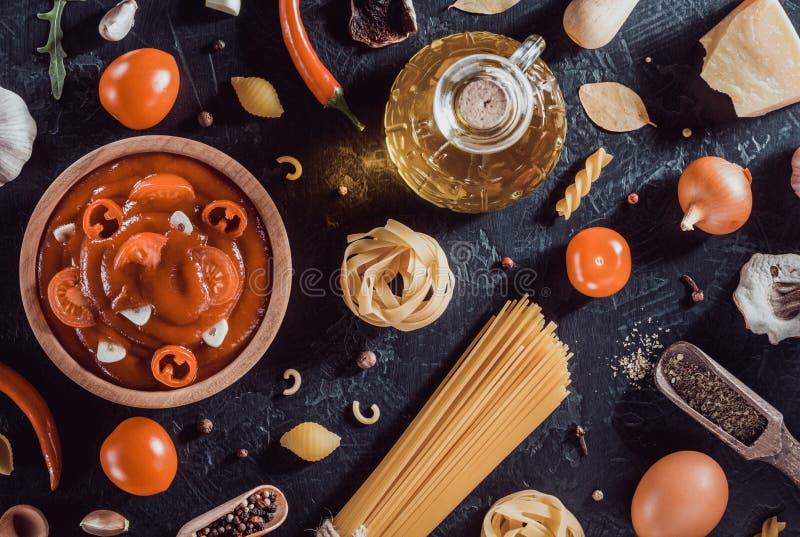 molho de tomate na bacia e na massa no preto imagem de stock royalty free