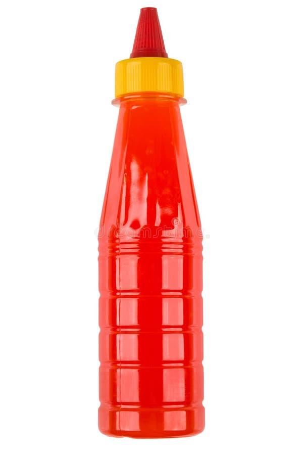 Molho de tomate quente na garrafa plástica vermelha isolada no branco imagem de stock