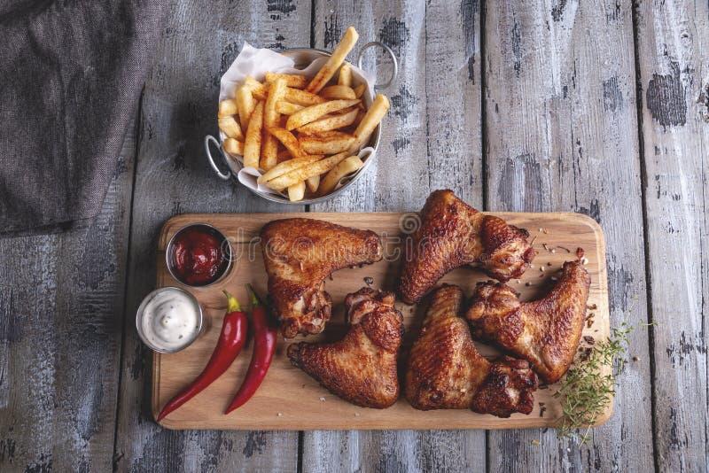 Molho grelhado das asas de galinha, das batatas fritas, o branco e o vermelho em uma superfície de madeira fotos de stock royalty free