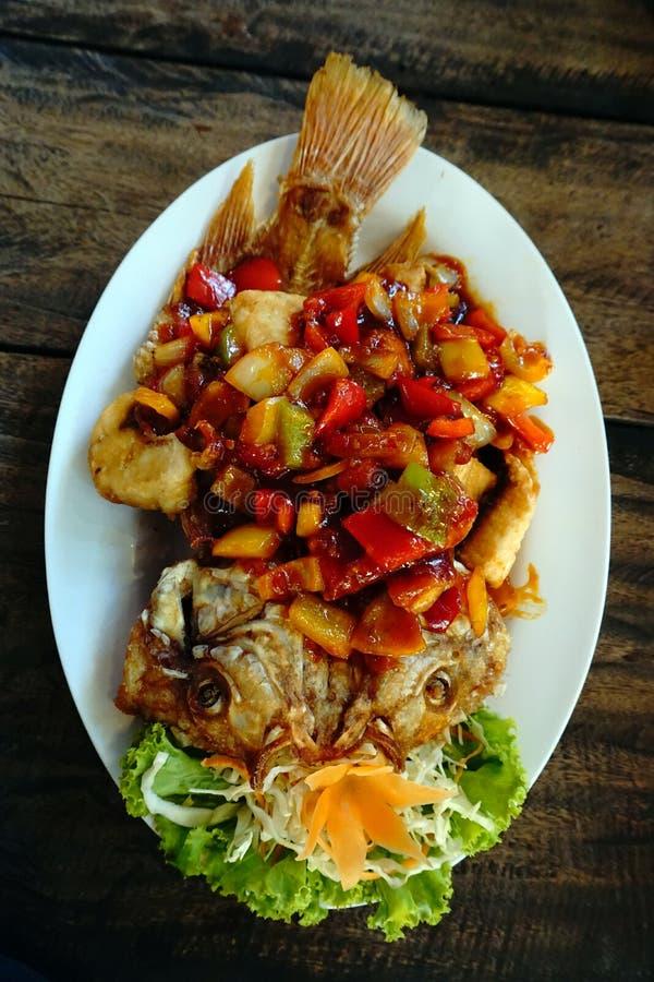 Molho picante friável e delicioso dos peixes inteiros fritados em uma tabela de madeira fotografia de stock royalty free