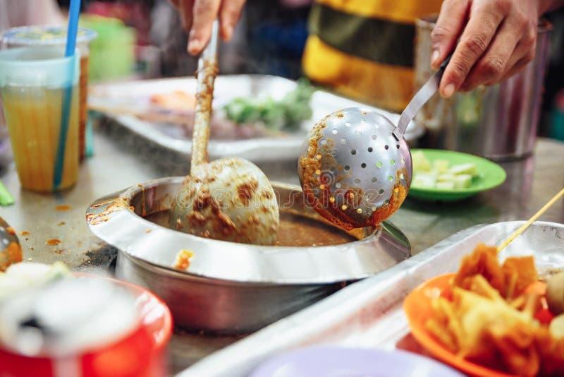 Molho satay de aquecimento no potenciômetro Satay é um prato da carne grelhada skewered com origens do Javanese na cidade de Mala fotos de stock