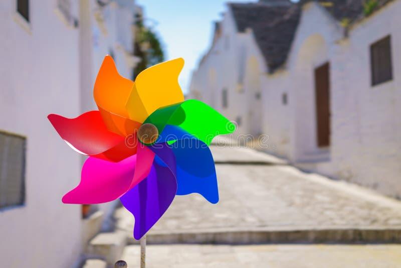 Molinillo de viento colorido del arco iris en día de verano del brillo del sol imagen de archivo libre de regalías