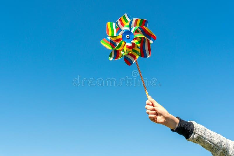 Molinillo de viento colorido del control del ni?o en fondo del cielo foto de archivo